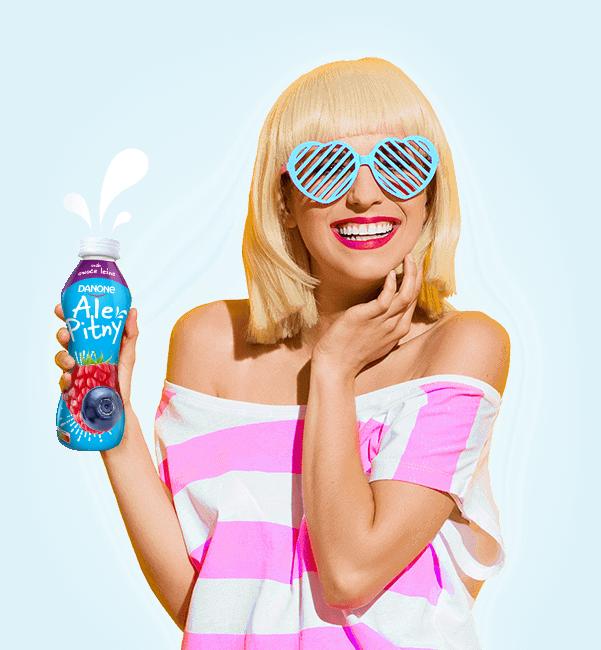 Uśmiechnięta kobieta w okularach w kształcie serduszek trzyma jogurt Ale Pitny z edycji limitowanej o smaku: ananas kokos